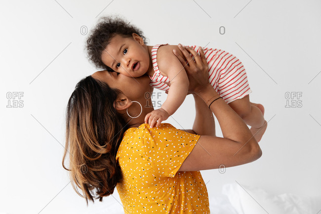 Mother lifting her baby in the air and kissing him