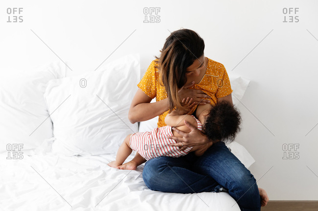 Mother nursing her baby on white bed
