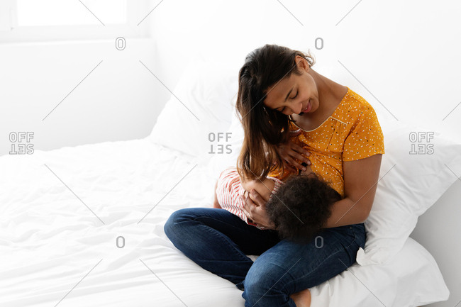 Smiling mother breastfeeding her baby on white bed