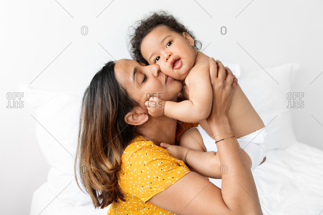 Mother holding her baby against her face and kissing him