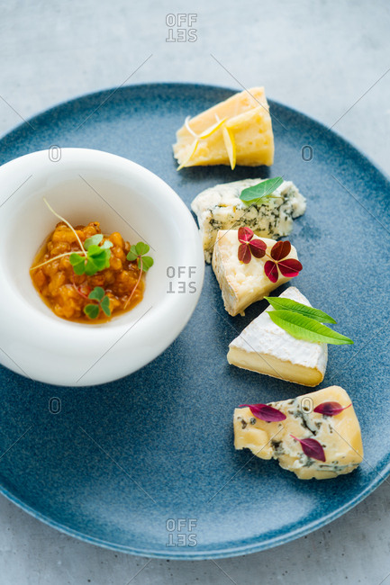 Overhead view of a cheese appetizer on blue plate
