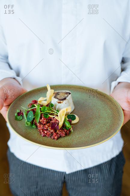 Chef holding gourmet tartare dish with bone