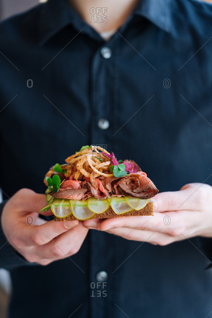 Chef holding  gourmet meat dish topped with onion straws