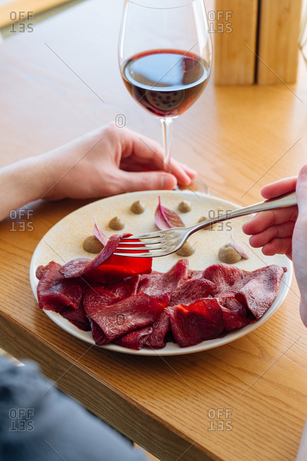 Person eating a gourmet meat dish with red wine