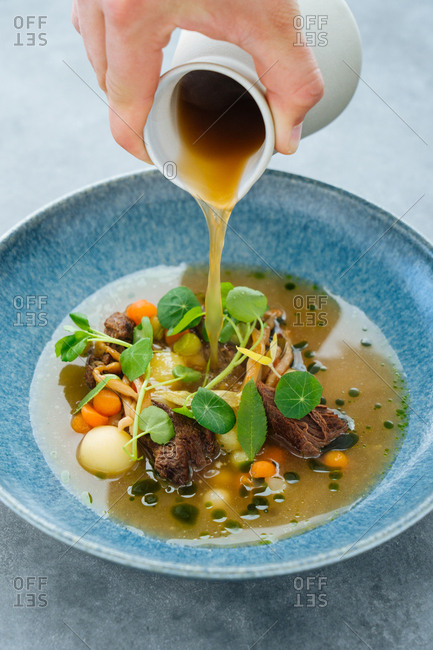 Hand pouring broth over beef and veggie dish