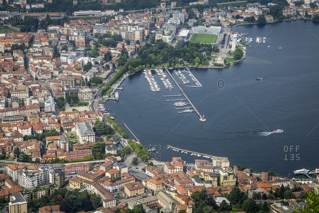 An aerial view of a boat leaving Como's harbor and travelling onto Lake Como. Lombardy, Italy.