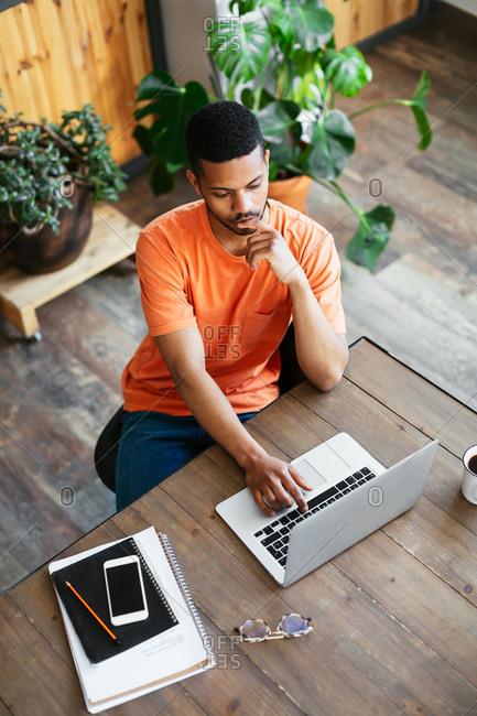 Young designer at wooden desk working on laptop.