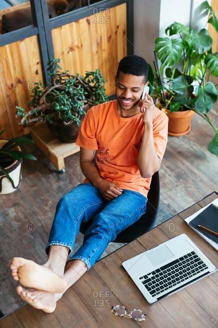 Smiling designer at wooden desk talking on phone.