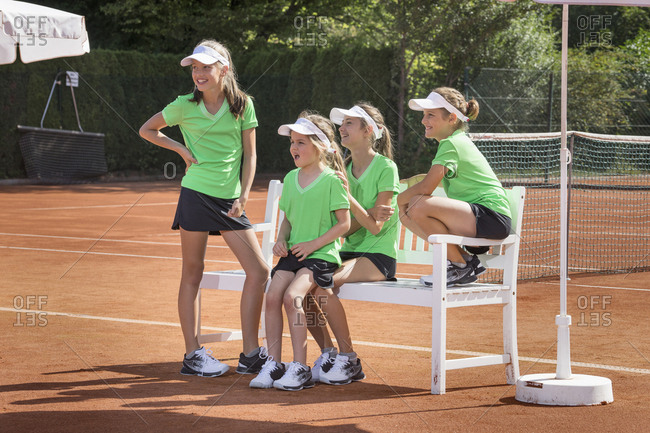 Group of young girls watching match on tennis court, Bavaria, Germany