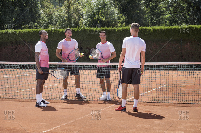 Group of young men playing tennis on a sunny day, Bavaria, Germany
