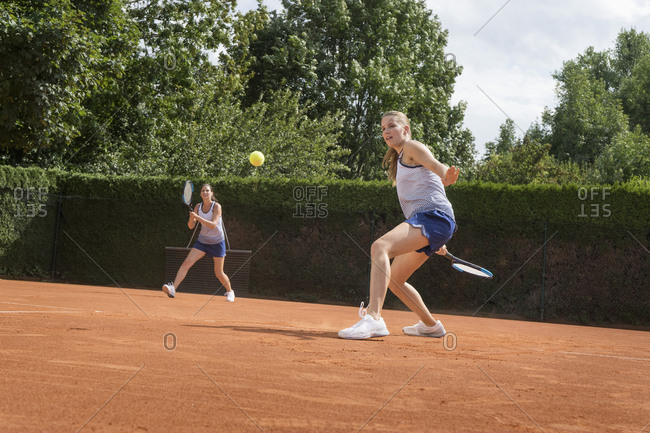 Two women playing tennis on a sunny day, Bavaria, Germany