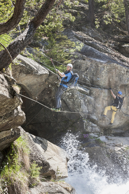 Men climbing rock via ferrata towards Stuibenfall Waterfall, Otztal, Tyrol, Austria