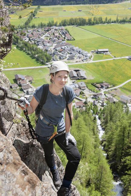 Woman climbing on rock via ferrata towards Lehner Waterfall, Otztal, Tyrol, Austria