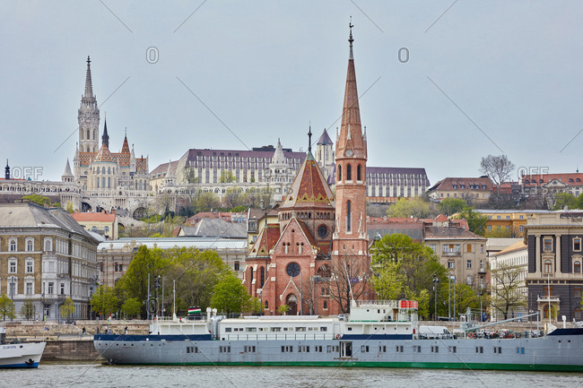 April 15, 2018: Matthias Church and Reformed church with docked ship on Danube river, Budapest, Hungary