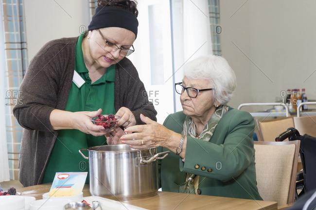 Nurse preparing food with senior woman in rest home
