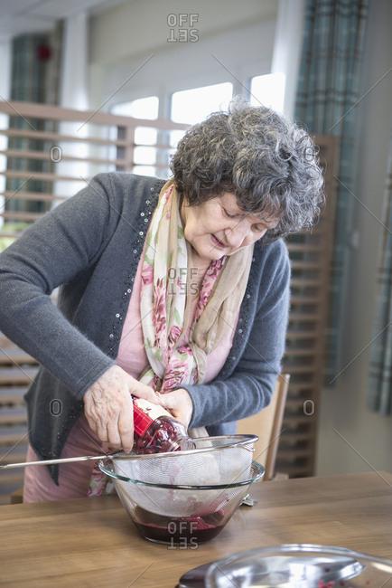 Senior woman preparing dessert in rest home