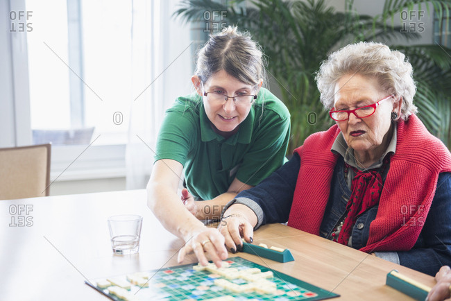 Nursing staff assisting senior woman playing scrabble board game