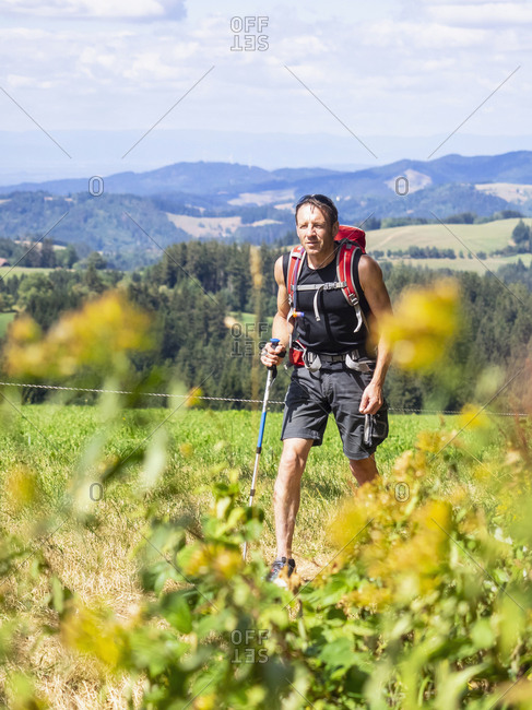 Male hiker passing by typical Black Forest farmhouse, Baden-Wurttemerg, Germany