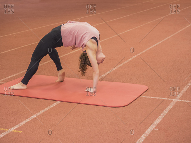 Woman bending over backwards in yoga position at athletics hall on tartan track, Offenburg, Baden-Wurttemberg, Germany