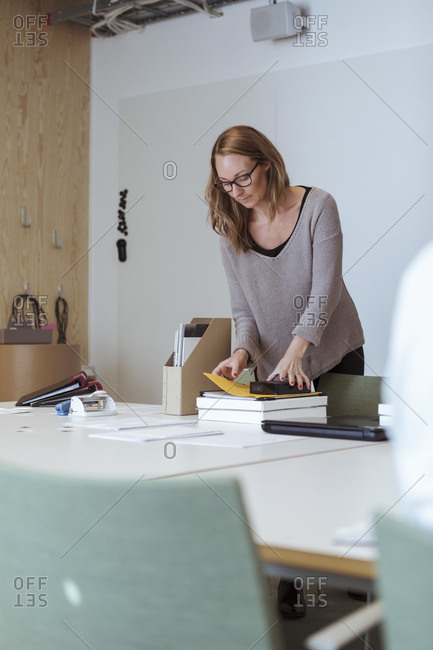 Mid adult female executive examining files on conference table at office