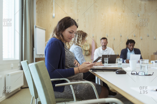 Pregnant businesswoman using mobile phone while sitting with colleagues in board room