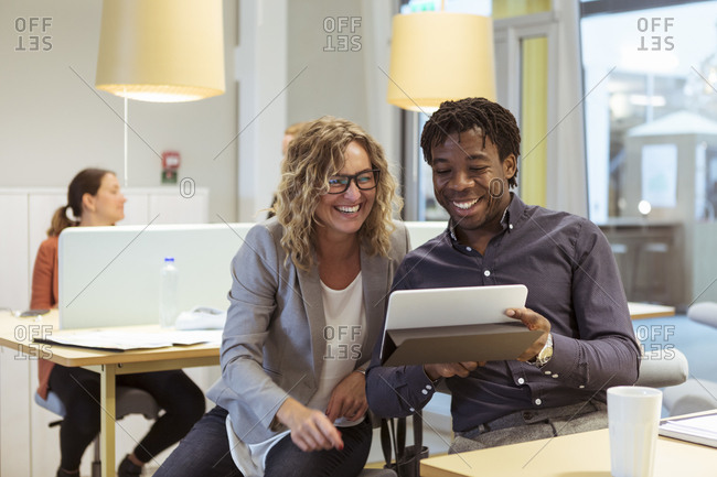 Smiling multi-ethnic coworkers looking at digital tablet in office