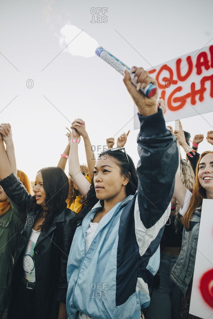 Low angle view of women holding hands while protesting for human rights against sky