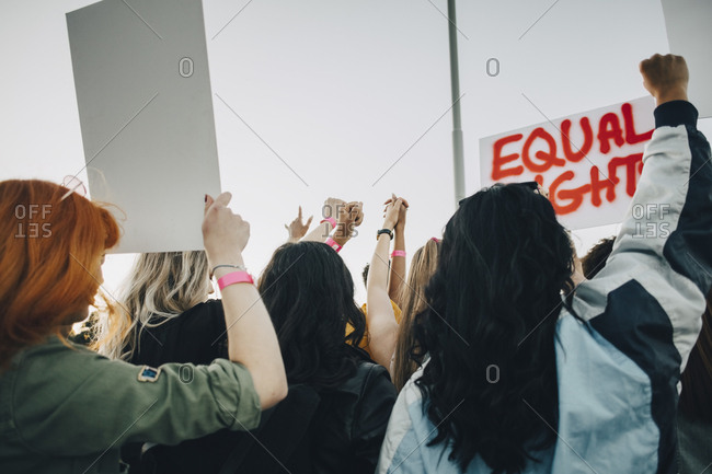 Rear view of women protesting for equal rights against sky in summer