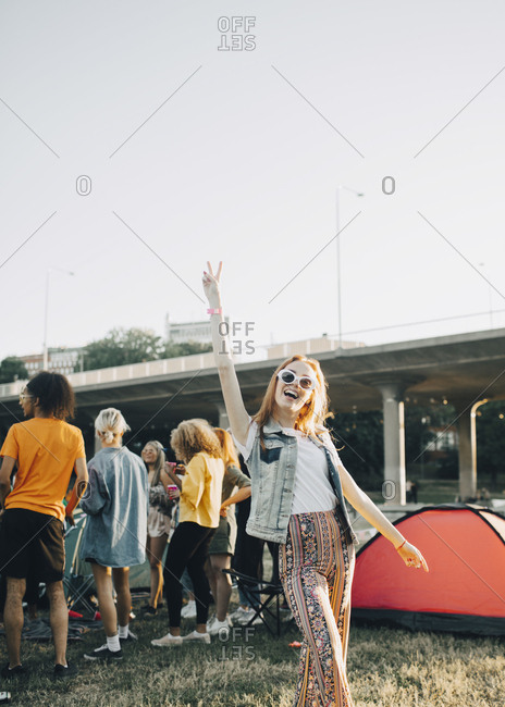 Portrait of happy woman enjoying with friends in festival against clear sky