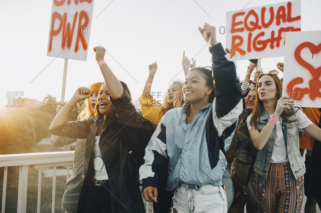 Young women shouting while protesting for equal rights against sky