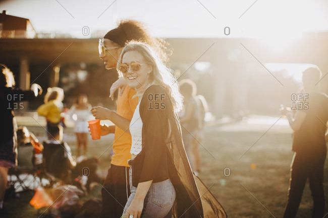 Smiling woman walking with friend at concert