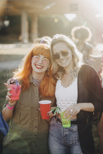 Portrait of smiling male friends enjoying drinks in concert on sunny day