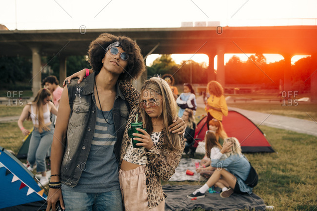 Fashionable friends with people in background at music event