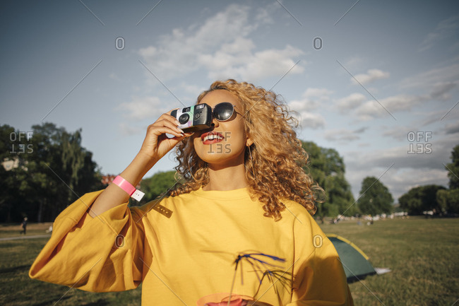 Smiling young woman photographing with camera on field against sky