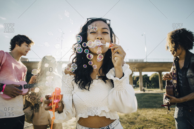 Woman blowing soap bubbles while friends playing ukulele during music event