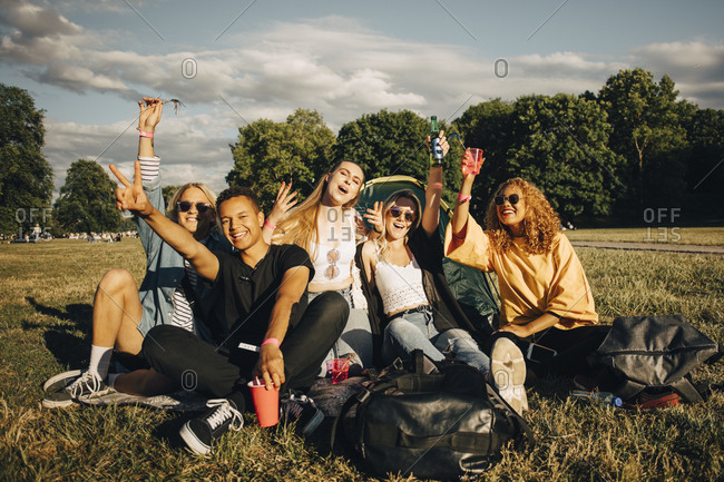Happy young friends enjoying while sitting on grass at music concert