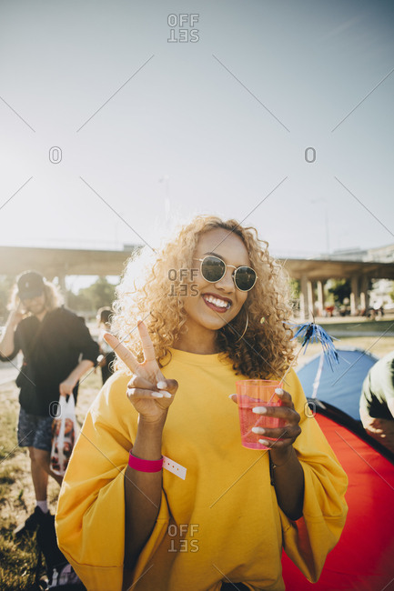 Portrait of smiling woman gesturing while enjoying drink in music festival