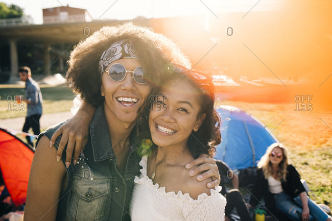 Portrait of smiling friends enjoying at music festival during summer