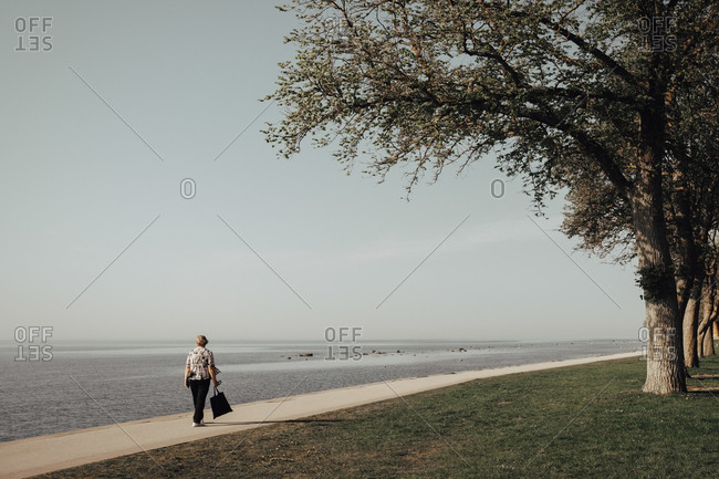 Full length rear view of senior woman walking on promenade by sea