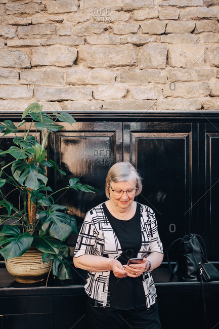Senior female tourist using smart phone while standing against stone wall at restaurant