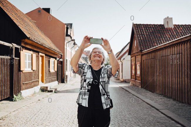Smiling senior woman photographing while standing on road in city against clear sky