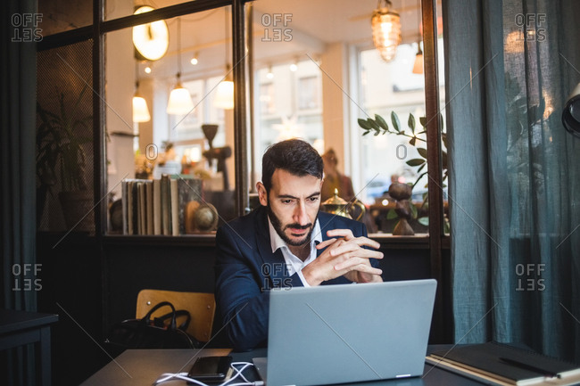 Confident businessman with hands clasped looking at laptop on desk in creative office