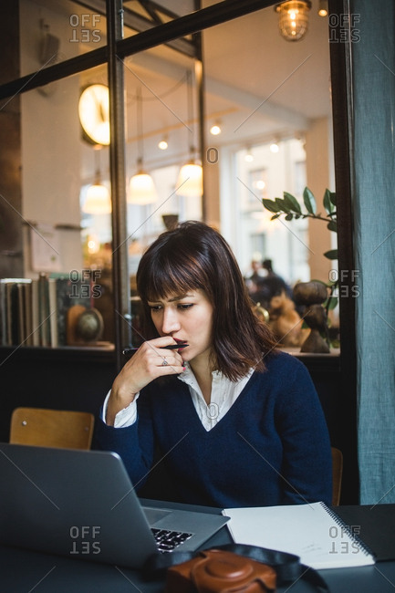Female business professional working at desk while using laptop in creative office