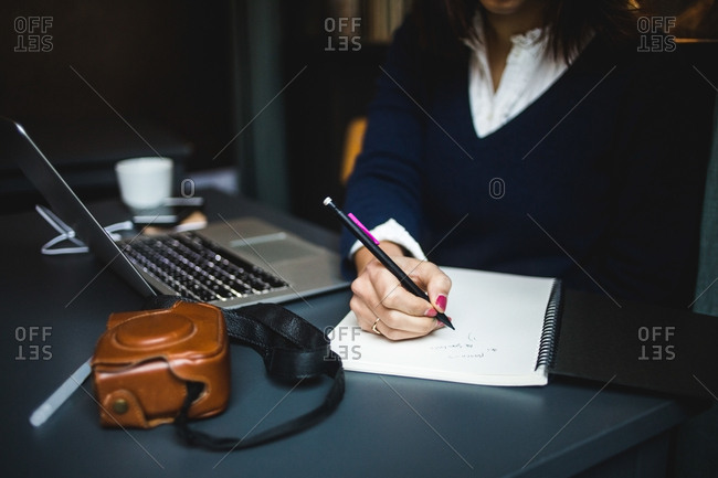 Midsection of businesswoman writing in diary at desk