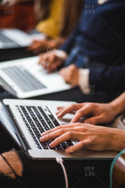 Midsection of colleagues using laptops in creative office