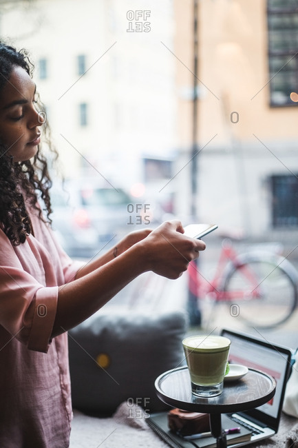Young female blogger photographing tea and snack on table through smart phone at creative office