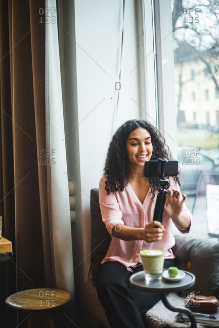 Smiling young female influencer vlogging through mobile phone on tripod sitting by window at creative office