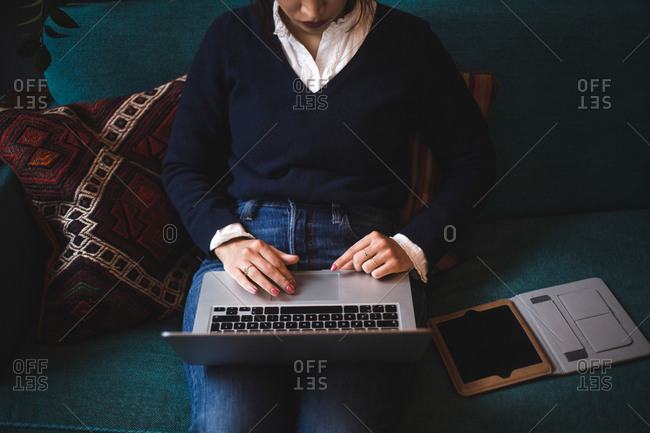 Midsection of female professional using laptop sitting on sofa at office