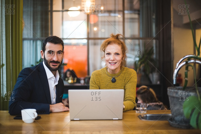 Portrait of smiling female and male business colleagues sitting with laptop at table in office
