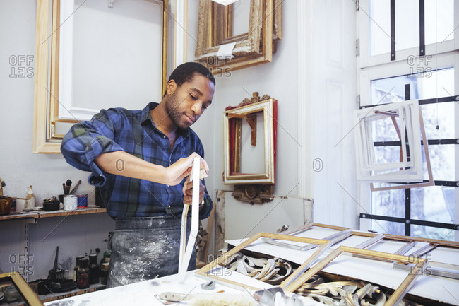 Confident young male craftsperson rubbing sand paper on frame at workshop